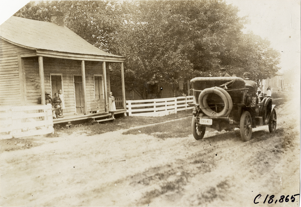 Motorists in automobile passing wooden-frame house, 1906 Glidden ...