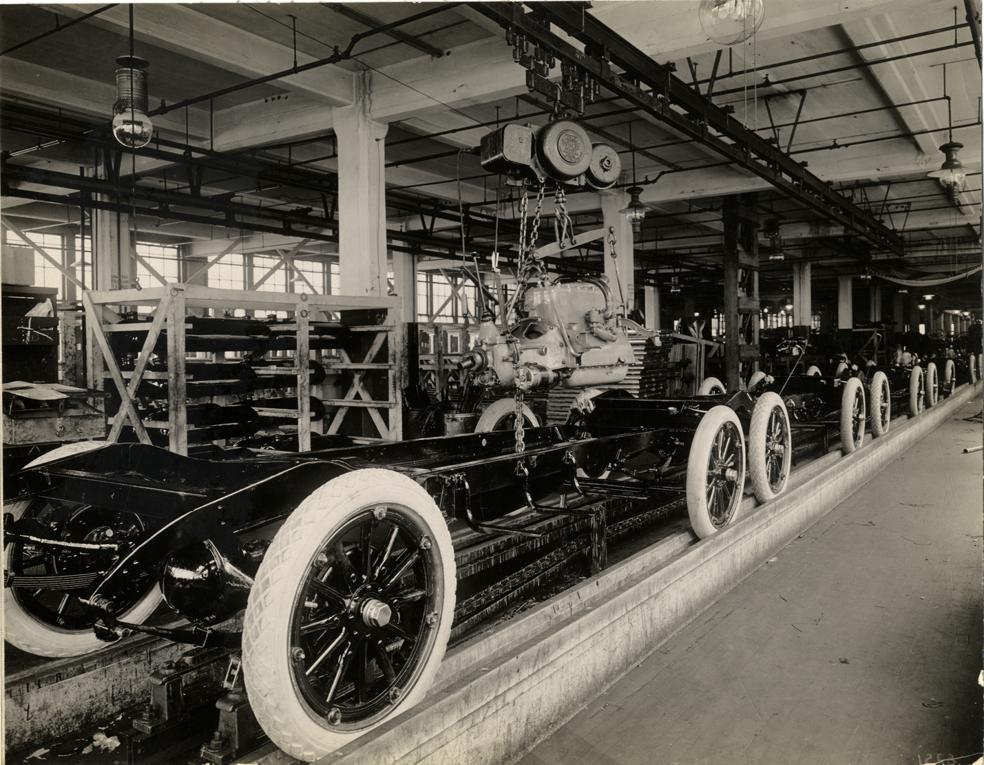 Engine being lowered onto automobile chassis, Chalmers Motor Company factory